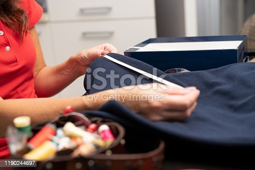 Sewing. Mom is at home. Woman with tape measure taking measurements to make a trouser hem.
