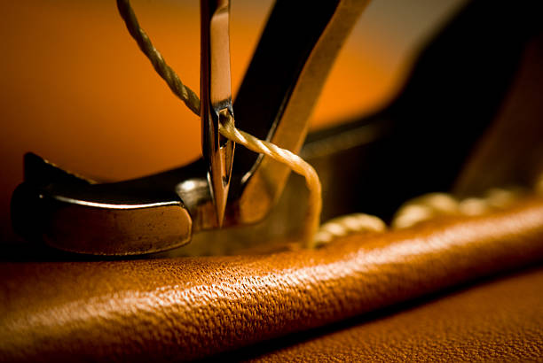 sewing needle of sewing machine making stitches - sewing machine needle stock photos and pictures