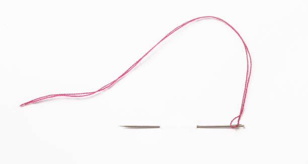 Sewing needle with red thread through the white background Sewing needle with red thread through the white background sewing needle stock pictures, royalty-free photos & images