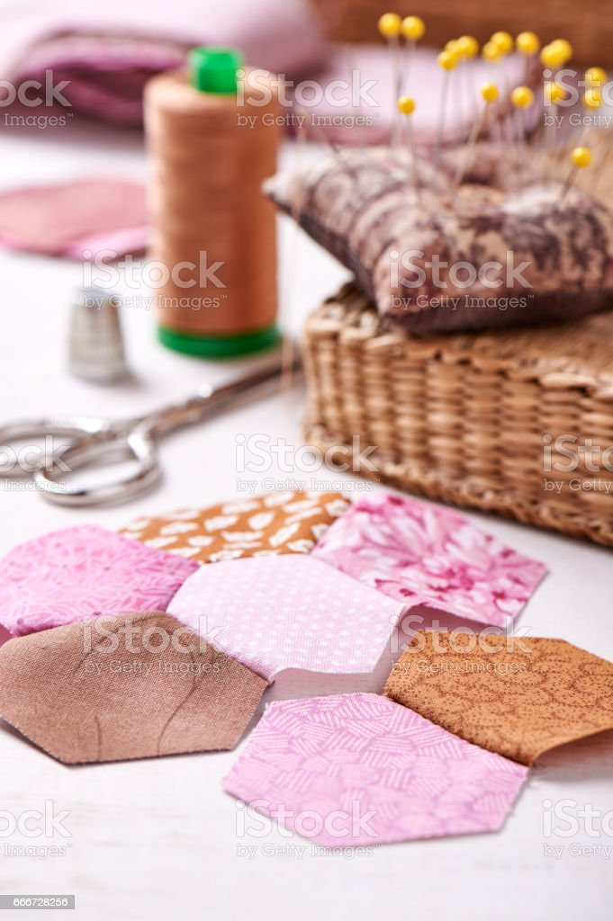 Sewing of hexagon pieces of fabric a quilt Grandmother's Flower Garden stock photo