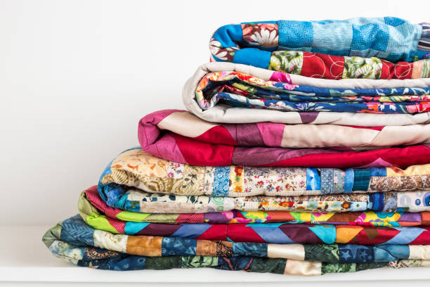 sewing, patchwork and fashion concept - beautiful colorful quilts were neatly folded and stored in several rows in height for storage, sale of finished textile stitched products on white background - quilt stock photos and pictures