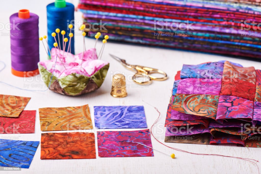 Sewing patchwork blocks to colorful batik quilt stock photo
