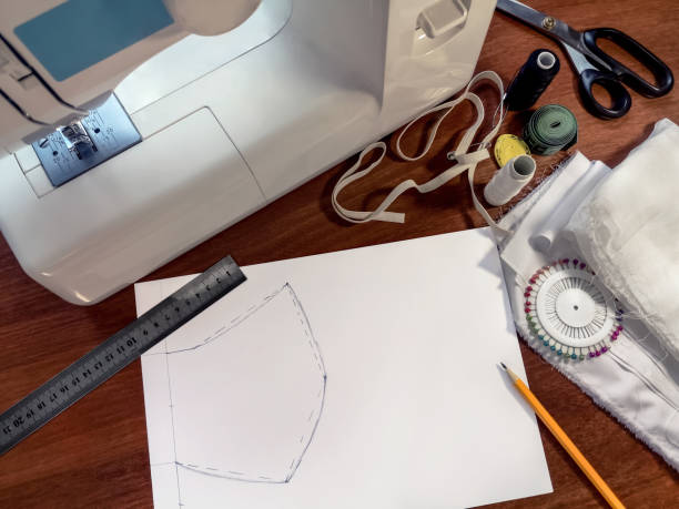 Sewing pattern of a medical protective face mask, painted on a white sheet of paper, lies on a brown surface of table on background of sewing accessories stock photo
