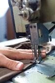 Hands work a sewing machine