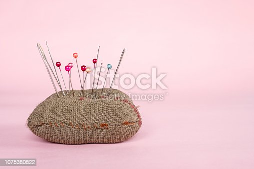 istock sewing pins on pink background. 1075380822