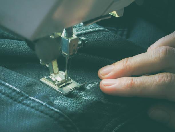 Plano de processo de costura na máquina de costura. O pé calcador e a agulha da máquina de costura durante a operação. - foto de acervo