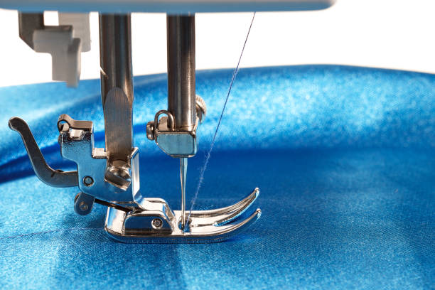 sewing process, sewing machine makes a seams on blue fabric, closeup side view - sewing machine needle stock photos and pictures