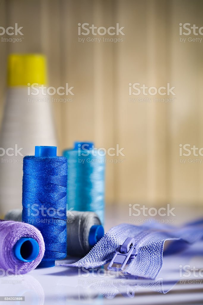 sewing spools and zip on table stock photo