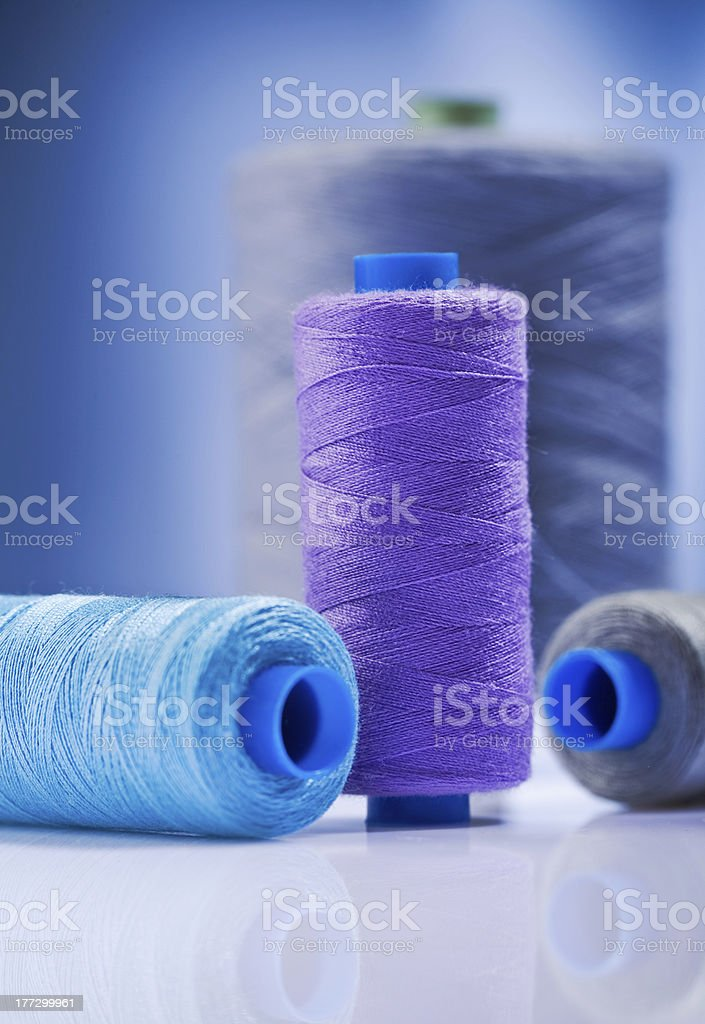 sewing spools on  blue background stock photo