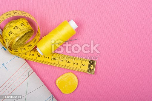 Spool of thread, chalk and measuring tape of yellow color on a pink background. Sewing accessories, patterns and accessories for needlework, sewing, embroidery, place for text, top view, Flat Lay, Copy space