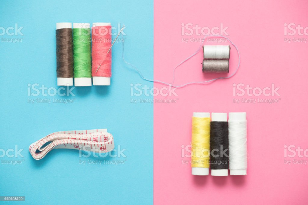 Sewing thread, needle, and meter on rose quartz serenity blue background. Directly above view.