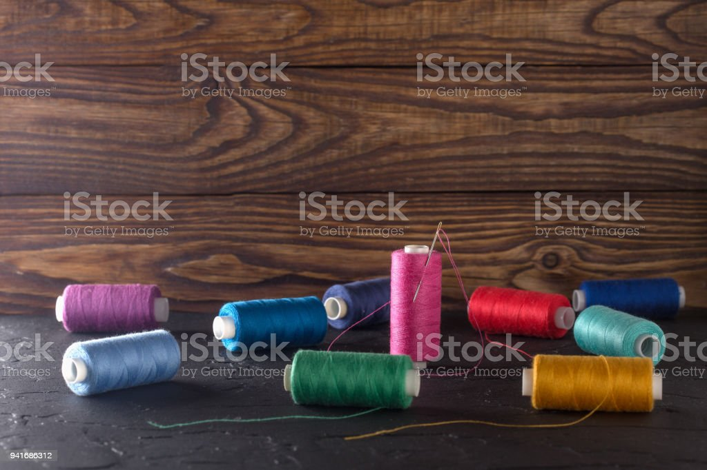 Sewing thread on coils, fabric, needles for sewing on wooden background. Set for tailoring products, knitting, hobbies and handmade, dressmaker, sewing accessories. stock photo