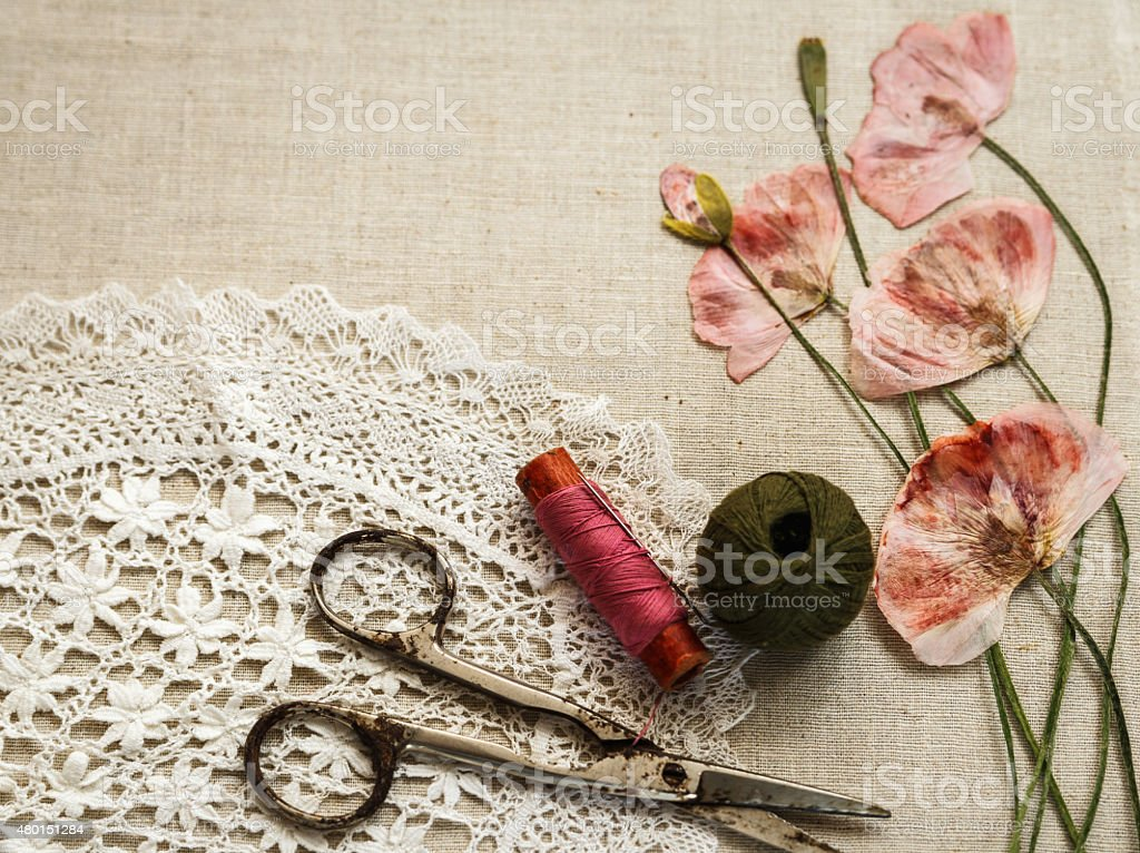 Sewing tools on linen cloth with lace and dry poppies stock photo