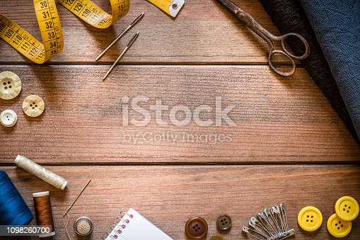istock Sewings supplies frame on rustic wooden table 1098260700