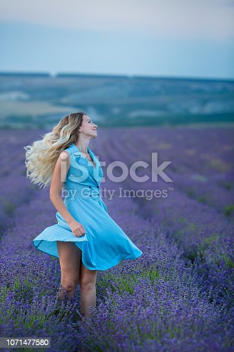 873786782 istock photo Sex appeal blond woman in airy blue dress enjoy life time vacation on fresh lavender field by walking or spinning around. Sylph attractive lady dancing on flowers. 1071477580