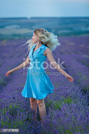 istock Sex appeal blond woman in airy blue dress enjoy life time vacation on fresh lavender field by walking or spinning around. Sylph attractive lady dancing on flowers. 1071478000