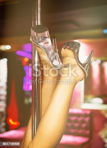 Sexual female performing striptease in night club.
