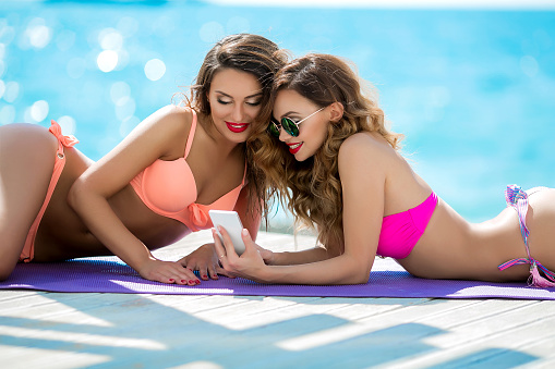 1155046257 istock photo Sexual girl in a bright bikini on a sunny beach. Bikini, red lips, blue sea, tanned girl. Two friends have a rest on the sea, make selfie, use a mobile phone 1127600880