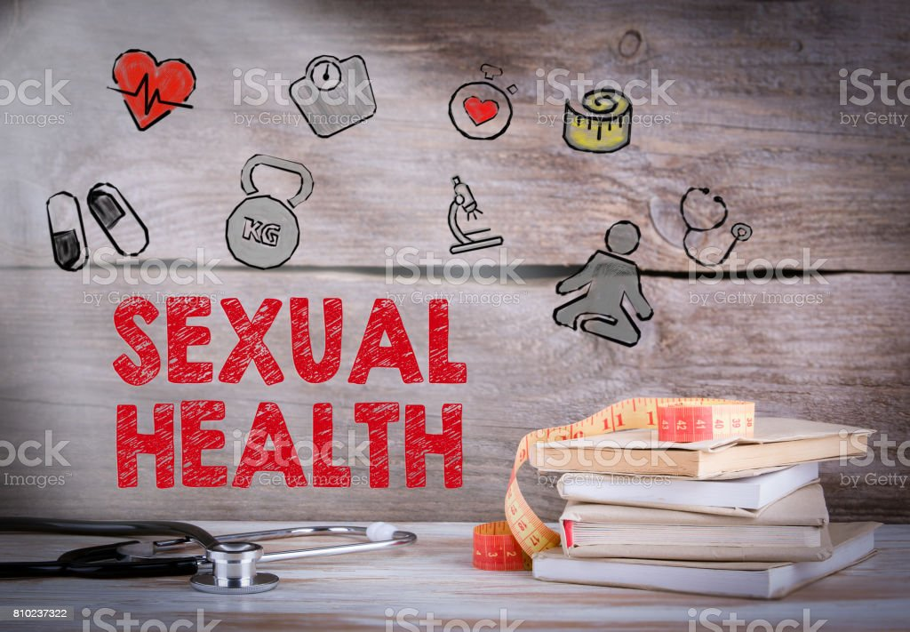 Sexual Health. Stack of books and a stethoscope on a wooden background stock photo