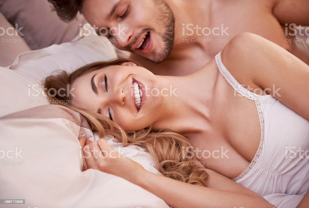 Sexual scene of passionate young couple in the bedroom stock photo