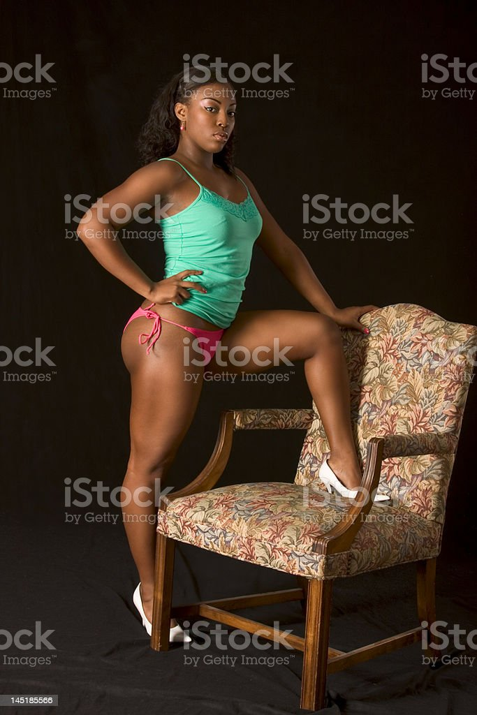 Sexy African-American girl by chair royalty-free stock photo