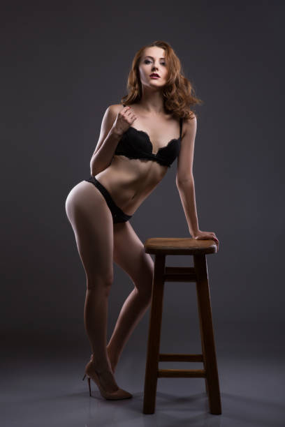 Sexy and beautiful young woman withwavy hair, long legs and bronzed skin is posing in the black lacy underwear in the studio on the chair, dark background stock photo