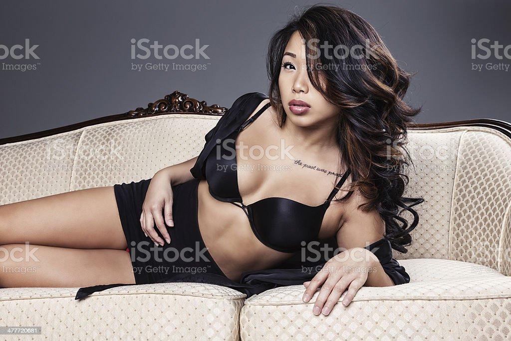 ca7116e8b Modelo asiática Sexy em Lingerie posando em preto antigo sofá foto  royalty-free