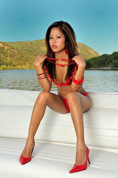 Modèle asiatique Sexy assise sur un banc dans un yacht - Photo