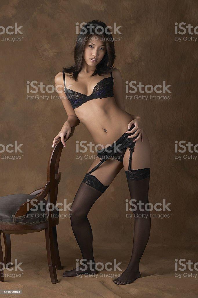 Sexy Asian woman in black lingerie by chair stok fotoğrafı