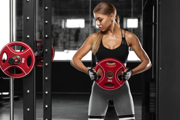 Sexy athletic girl working out in gym. Fitness woman doing exercise stock photo