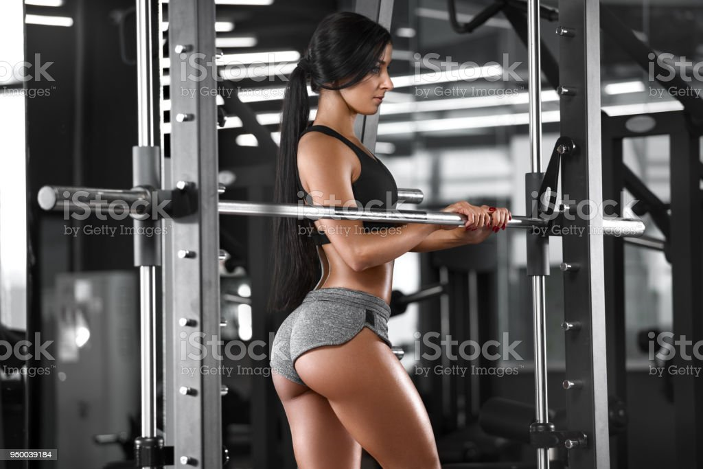 Sexy athletic girl working out in gym. Fitness woman doing exercise. Sexy beautiful butt in thong stock photo