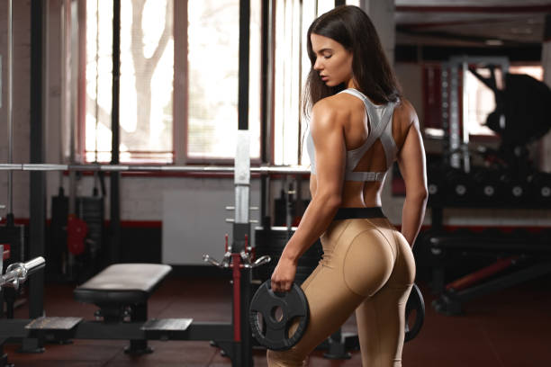 Sexy athletic girl workout in gym. Fitness woman doing exercise. Beautiful butt in leggings stock photo