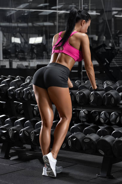 Sexy athletic girl workout in gym. Fitness woman doing exercise. Beautiful butt in thong stock photo