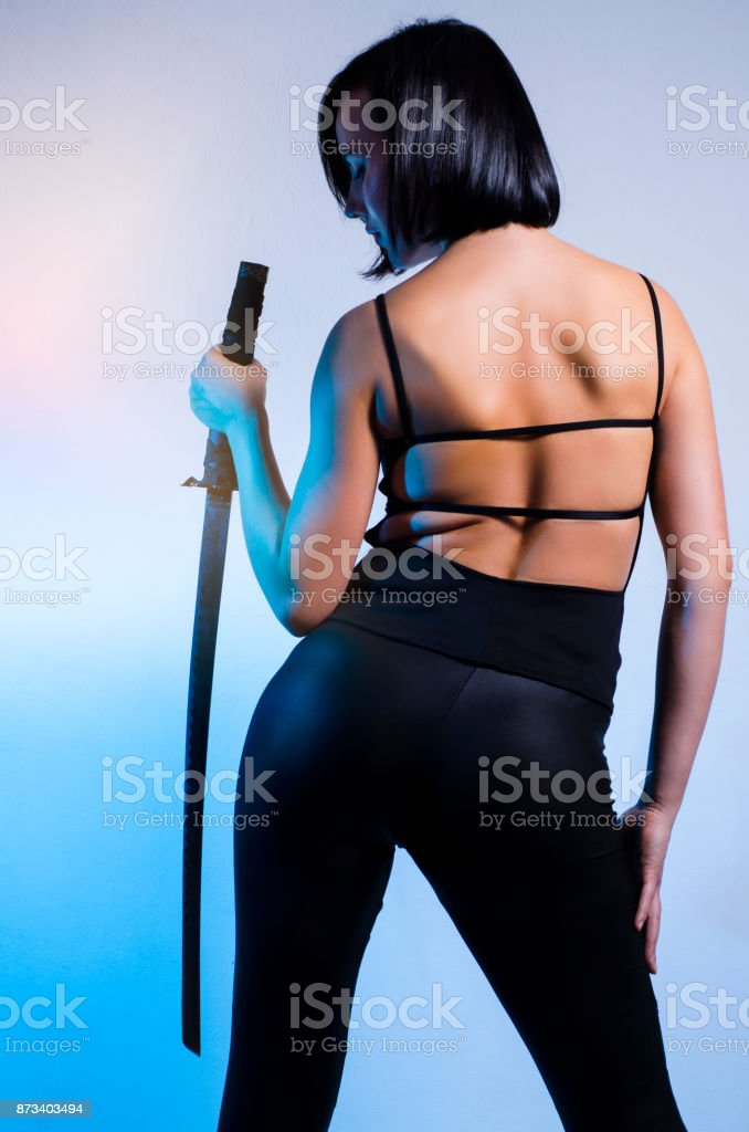Sexy, attractive black hair woman holding sword stock photo