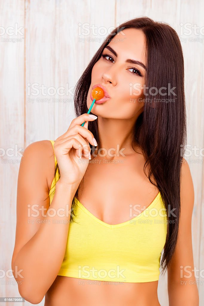 Sexy attractive brunette  licking sweet sugar candy stock photo