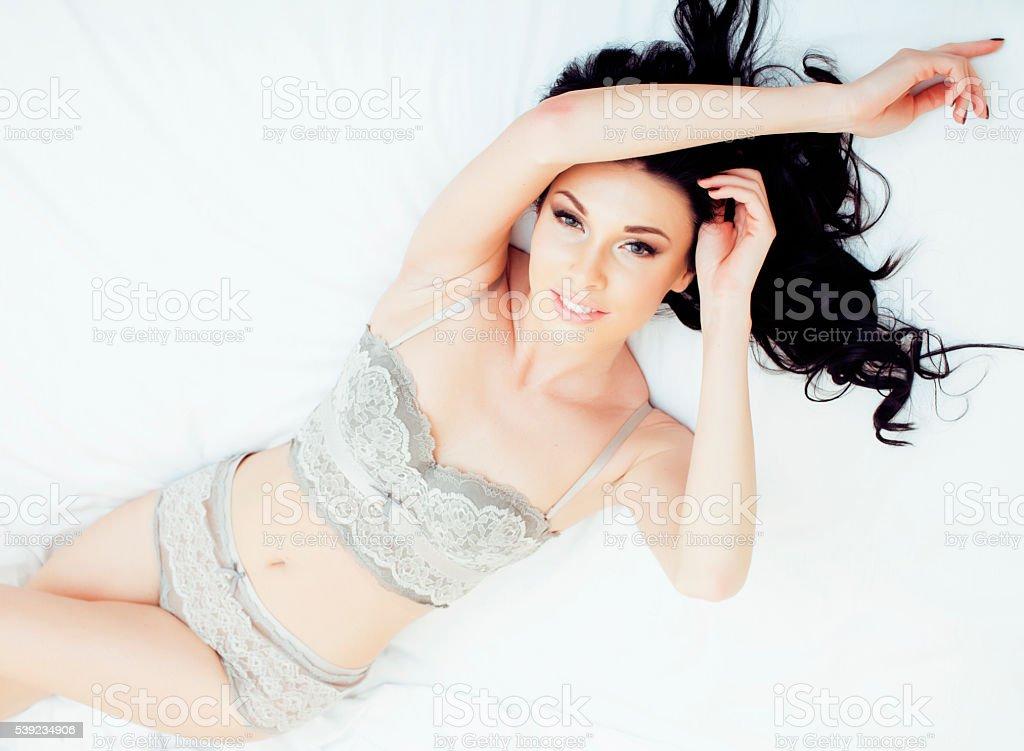 Sexy beautiful brunette woman lying in bed wearing sensual gray foto royalty-free