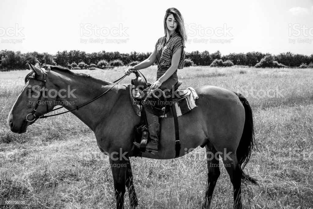 Sexy, beautiful, cowgirl with blue eyes riding horse with western saddle in field of grass on ranch stock photo