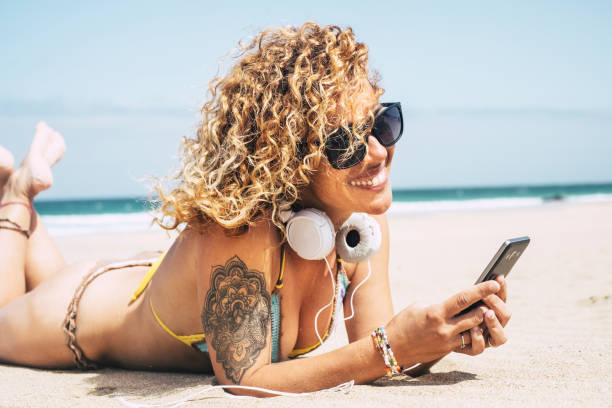 sexy beautiful curly hair caucasian middle age lady in bikini laying at the beach with the blue ocean in background. vacation leisure activity listening music with headphone and phone. cheerful cute lady in vacation enjoying summer sexy beautiful curly hair caucasian middle age lady in bikini laying at the beach with the blue ocean in background. vacation leisure activity listening music with headphone and phone. cheerful cute lady in vacation enjoying summer middle aged women in bikinis stock pictures, royalty-free photos & images