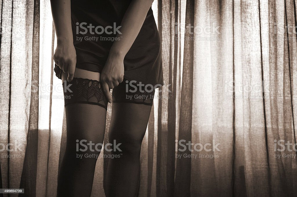 Sexy, beautiful legs in fashionable stockings , curtains in backgraound, sepia stock photo