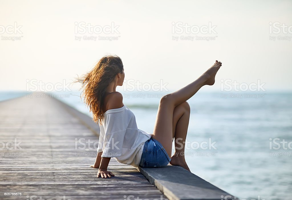 Sexy beautiful woman relaxing on pier with sea view stock photo