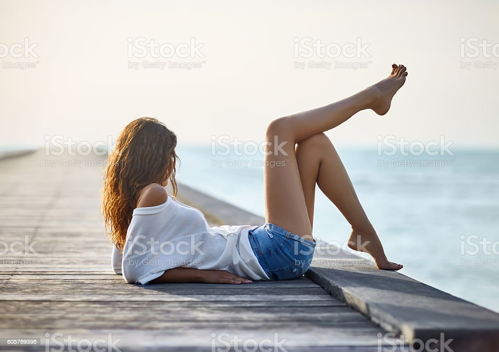 Sexy beautiful woman relaxing on pier with sea view – Foto
