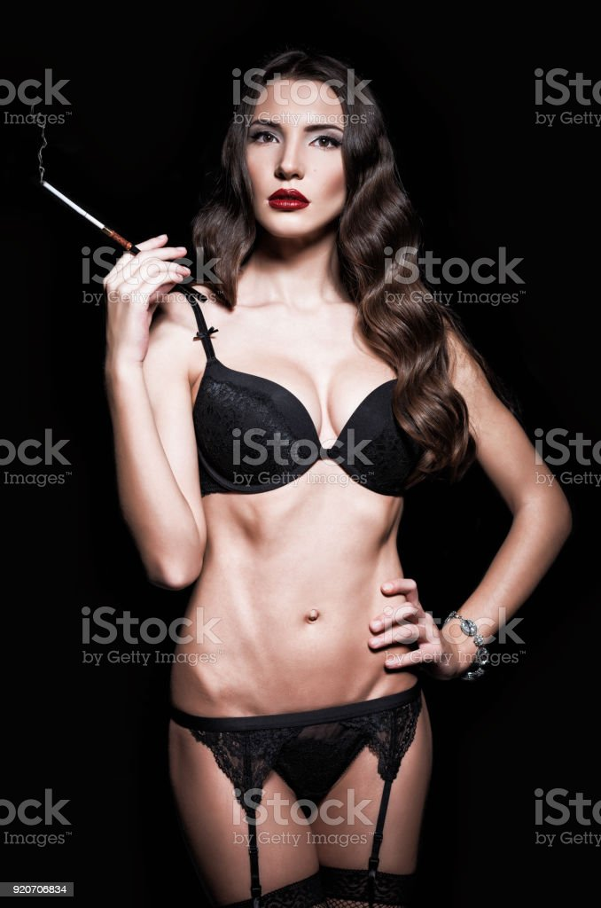 cd7754943ec Sexy beautiful young woman in lingerie smoking cigarette. Retro style photo  - Stock image .