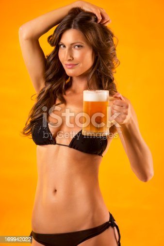 Attractive young woman having a beer, looking at camera, very sexy