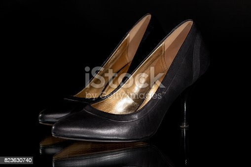 istock Sexy black leather woman's classic stiletto high heel court shoes. Moody fashion close up. 823630740