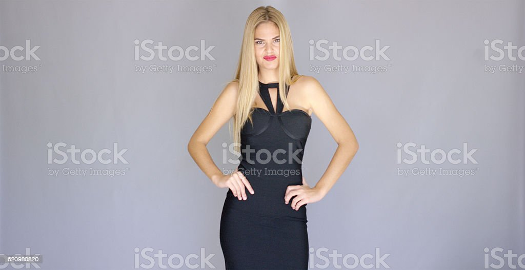 Sexy blond model posing in evening dress over gray foto royalty-free