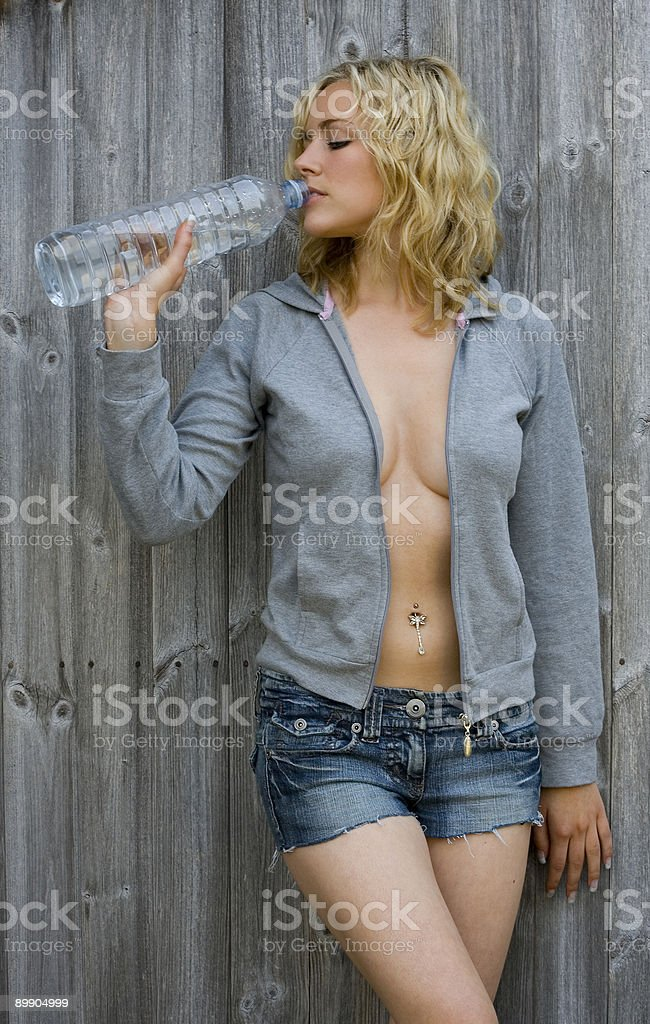 Sexy Blond Woman or Girl Drinking Bottle of Water royalty free stockfoto