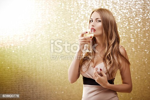 istock sexy blond woman with a glass of champagne at party 628800776