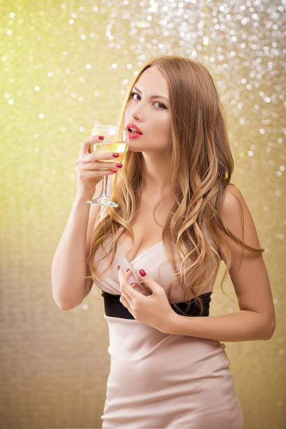 sexy blond woman with a glass of champagne at party stock photo