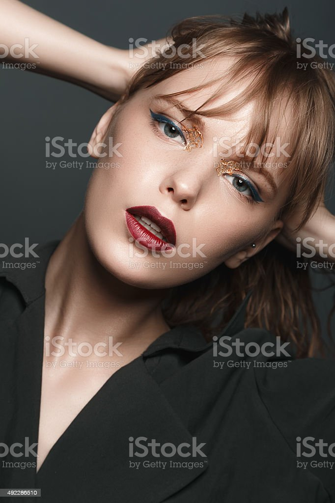 Sexy blonde girl with red lips and gold on eyes stock photo