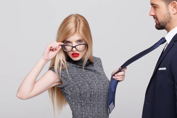 Sexy blonde manipulator woman pulling man by tie stock photo